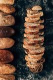 loafs e partes de pão arranjados no tabletop escuro Fotografia de Stock Royalty Free