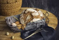 Loafs of rye bread in a basket with chicken eggs on the table. The Loafs of rye bread in a basket with chicken eggs on the table Royalty Free Stock Image