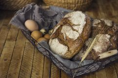 Loafs of rye bread in a basket with chicken eggs on the table. The Loafs of rye bread in a basket with chicken eggs on the table Royalty Free Stock Photo