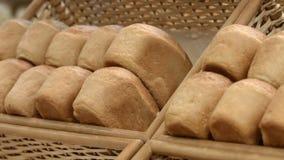 Loafs of white bread. Fresh bread in a box on a supermarket shelf stock video