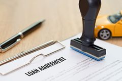 Loan agreement document with rubber stamp and car model toy on w. Ooden desk stock photo