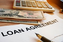 Loan agreement, money and calculator on a desk. Loan agreement, money and calculator on an office desk Stock Photography
