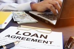 Loan agreement and money on a desk. Loan agreement and money on the desk royalty free stock images