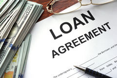 Loan agreement on a table. Loan agreement on a table and dollars royalty free stock photography
