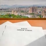 Loan application. Paper on desk near window and cityscape far away Royalty Free Stock Image