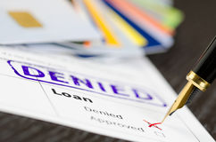 Loan application close up shot and stamp denied, cards and pen. royalty free stock images