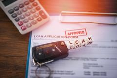 Loan approval - financial loan application form for lender and borrower for car with key and calculator on the table office stock images