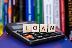 Loan. Calculator with the word Loan written in wooden block letters stock images