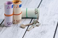 Loan contribution or estate deal concept. Three roll stacks of european union currencies - large sum in cash - and a key bunch on wooden background as a concept Royalty Free Stock Photo