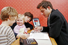 Loan series. Bank manager with mother and her two children wanting a loan stock image
