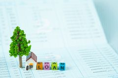 LOAN text and small model house and little tree with notebook, s. Avings banking, loan for house and real estate concept idea stock image