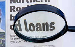 Loans. A macro  image of the word loan in a newspaper headline emphasized by a magnifying glass Stock Photos
