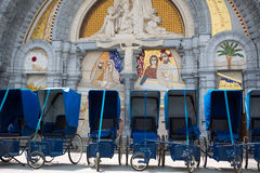Loans of blue wheelchairs in front of the church within the Sanc. Tuary in Lourdes, 2013. Every wheelchairs was a donation of a good fellow Christian. France Royalty Free Stock Photography