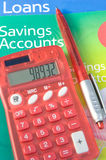 Loans and saving accounts. An image of a red plastic solar powered calculator on a card marked loans and savings together with a matching pen vector illustration