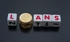 Loans. Text ' loans ' in red uppercase letters on white cubes with letter ' o ' replaced by a pile of pound coins dark background Royalty Free Stock Images
