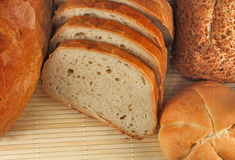 Loaves of bread and bread rolls. Loaves of bread, one sliced and bread rolls stock photography