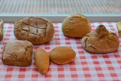 Loaves of bread on a checkered tablecloth. Image of loaves of bread on a checkered tablecloth stock photos