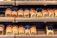 Loaves of bread. Of various kinds lined up on wooden shelves at a bakery royalty free stock photography