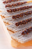Loaves and candied roasted nuts. Bread with candied roasted nuts laid out for them in chocolate, all on wooden cutting board royalty free stock photos
