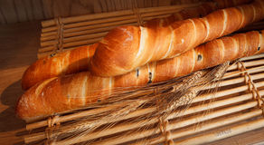 Loaves of French Baguettes. Long thin loaves of french bread - black olive baguettes on a bamboo tray with dried wheat stock photos