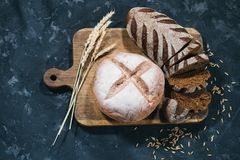 Loaves of fresh bread. Top view of composition with loaves of homemade bread and rye on wooden board on blue background home bakery concept stock images