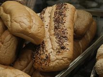 Loaves of freshly baked bread. Close up of sesame and flavored loaves of bread piled in a wicker basket stock image