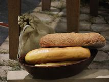 Loaves of freshly baked bread. Fresh loaves of bread in a round wooden bowl, with a sack beside it royalty free stock photos