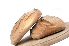 Loaves of rustic bread. A pair of leaves of rustic bread on a wood background stock images