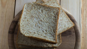 Loaves of whole wheat bread. On wooden block Stock Photos