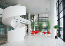 Lobby. Company lobby with spiral stair and red chairs Royalty Free Stock Image
