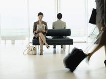 Lobby d'aéroport de Reading Newspaper At de femme d'affaires Photographie stock libre de droits