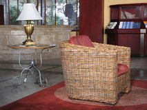 Lobby Decoration. Rattan chair and table lamp in a hotel lobby royalty free stock photo