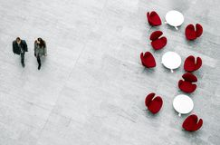 Lobby waiting area with armchairs, tables and pair of people. View from above of lobby with armchairs, tables and blurred pair of people passing by Stock Photography