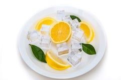 Lober av den nya, saftiga, ljusa gula citronen, kuber av uppfriskande is och gräsplansidor på en platta på en vit bakgrund isoler Arkivbilder