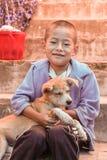 Lobesa村庄, Punakha,不丹- 2016年9月11日:小不丹男孩坐拥抱在街道的台阶一只流浪狗 免版税库存图片