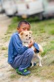 Lobesa村庄, Punakha,不丹- 2016年9月11日:拥抱在街道的不丹男孩德国波美丝毛狗小狗 库存照片