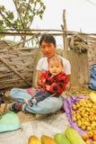 Lobesa村庄, Punakha,不丹- 2016年9月11日:有他的婴孩的未认出的人他的膝部的在每周农夫市场上 免版税图库摄影