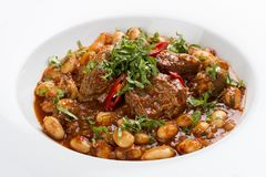 Lobio with beans and beef on a white plate. Lobio from green beans on a white plate on white background stock photography