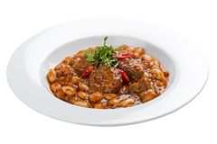 Lobio with beans and beef on a white plate. Lobio from green beans on a white plate on white background royalty free stock photo