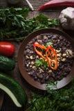 Lobio su un piatto, su un prezzemolo, su un cetriolo e su un pomodoro ceramici sui bordi marroni Fotografie Stock
