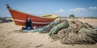 LOBITO, АНГОЛА - 9-ОЕ МАЯ 2014: Неопознанный ангольский рыболов сидя перед красной рыбацкой лодкой на сетях отладки пляжа Стоковая Фотография RF