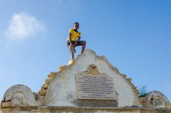 LOBITO, ANGOLA - MAY 09 2014: Unidentified African boy with yellow shirt standing on Reducto Sao Pedro Portuguese fort. LOBITO, ANGOLA - MAY 09 2014 Royalty Free Stock Photos