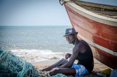LOBITO, ANGOLA - MAY 09 2014: Unidentified Angolan fisherman sitting in front of red fishing boat at beach fixing nets Stock Image