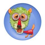 Lobo cansado hecho de verduras en la placa azul Imagenes de archivo