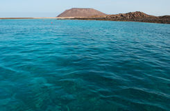 Lobos Island, Fuerteventura, Canary Islands, Spain, water, ocean, desert, landscape, volcano, mountain, beach. Crystal clear water and the Caldera mountain of Royalty Free Stock Images