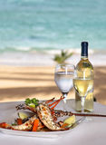 Lobster. On the grill with lemon, in sea background Royalty Free Stock Photo