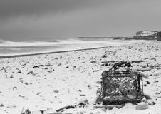 Lobster Beach. A lobster pot washed up during a storm is left stranded on a snow covered beach stock photo