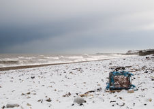 Lobster Beach. A lobster pot washed up during a storm is left stranded on a snow covered beach stock photography