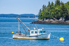 Lobster Boat at Anchor. A hard working lobster boat lays at anchor in a small harbor in the Down East region of Maine Royalty Free Stock Photo