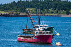Lobster Boat at Anchor. A hard working lobster boat lays at anchor in a small harbor in the Down East region of Maine Stock Photos